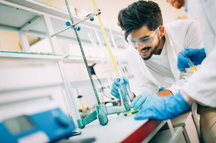 young-smiling-student-in-white-coat-doing-chemical-used-lab-equipment