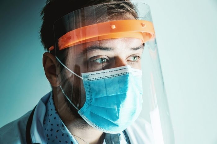 scientist in lab with COVID-19 protective gear mask and shield